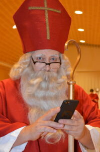 Samichlaus mit Mitra, Bischofstab und Smartphone. Katholische Kirche Küsnacht Erlenbach